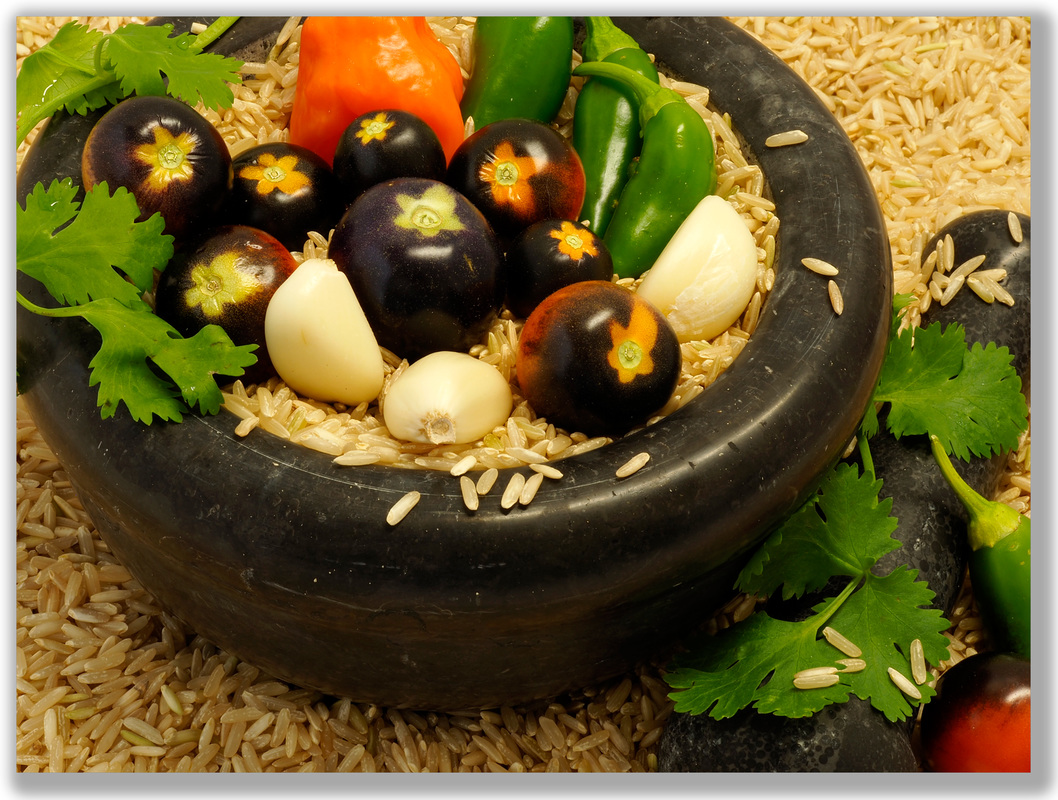 Photograph of a mortar and pestle with rice, tomatoes, jalapenos, and cilantro around it