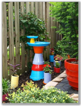 Photograph of a brightly painted, terra cotta pot birdbath