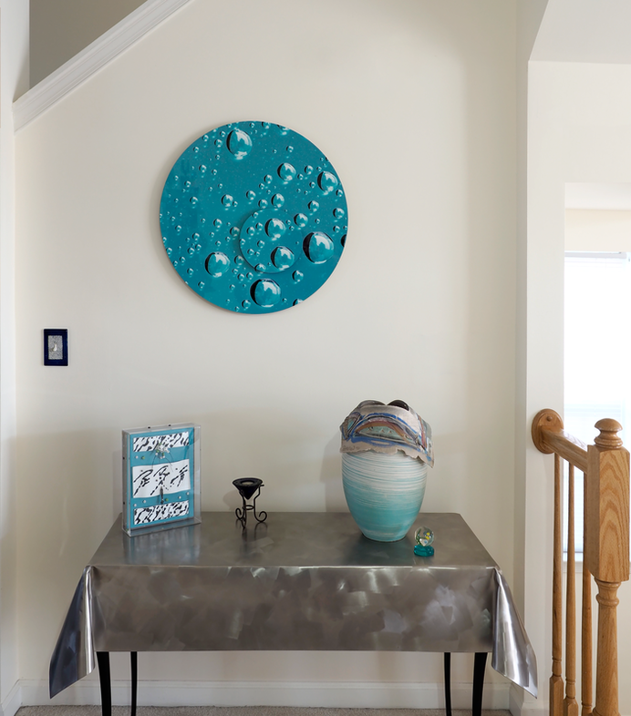 Round aluminum dimensional wall art showing water drops